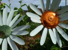 Metal daisies out of mini blind slats and pot lids. cute idea