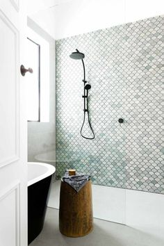Bathroom with seamless glass, a flush floor, fish tile in the shower, and a freestanding tub