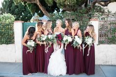 I LOVE this wedding. Burgundy dresses with white flowers v. white dress with dark flowers. Boys looking dapper in their navy suits and tan shoes w/ the groom wearing a colored shirt.