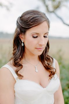 Katie May bridal gown and dangling bridal jewelry. Creek Club at I'On wedding photographed by Charleston wedding photographer Studio Adele.