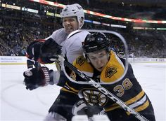 Ottawa Senators defenseman Marc Methot (3) checks Boston Bruins left wing Jordan Caron (38) into the boards in the second period of an NHL hockey game in Boston, Tuesday, April 2, 2013. (AP Photo/Elise Amendola)