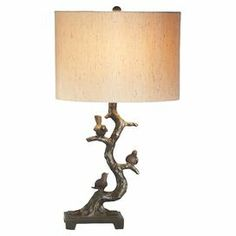 """Sculptural table lamp with a perched bird base and drum shade.    Product: Table lampConstruction Material: Resin and linenColor: Brown and tanFeatures: Bird and tree motifAccommodates: (1) 60 Watt bulb - not includedDimensions: 23"""" H x 13.5"""" Diameter"""