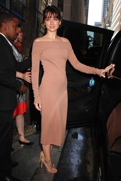 Ana de Armas wears a nude fitted off-the-shoulder Narciso Rodriguez frock, amped up by delicate hoop earrings and barely there coordinating sandals, highlighting her golden complexion.