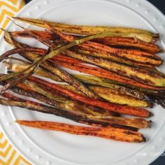 a white plate with rainbow colored yellow and orange glazed roasted carrots