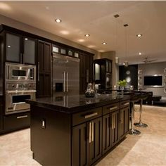 This kitchen is gorgeous.  The espresso colored cabinets are glamorous and the brushed nickel hardware adds style.  We love the small recessed lighting--so much more elegant than the large builder grade models.  Who wouldn't be able to cook an amazing dinner with these high end professional appliances.