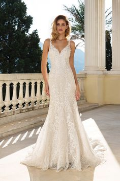 Allover sequined embroidered lace add a romantic vibe to this stunning fit and flare gown. With a V-neckline and illusion back, the gown is finished off with a chapel length train and unique scallop hem.