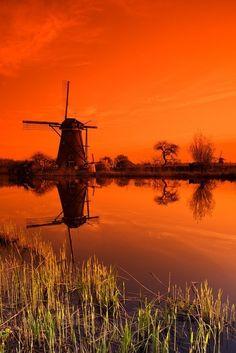 Beautiful orange sky over a Dutch windmill