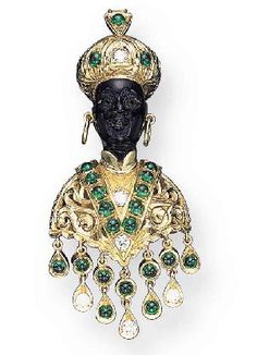 HARDSTONE, EMERALD, AND DIAMOND BLACKAMOOR BROOCH, BY NARDI. The hard stone Blackamoor wearing a textured turban set with a circular-cut diamond and cabochon emeralds, with gold ear hoops, the textured and openwork tunic set with circular-cut diamonds and cabochon emeralds, suspending a fringe of circular-cut diamonds and cabochon emeralds, mounted in 18K gold.