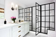 Chic black and white bathroom features a stunning walk in shower fitted with a steel glass enclosure, marble hex floor tiles, and white stacked surround tiles holding a brass shower kit facing a marble top bench.
