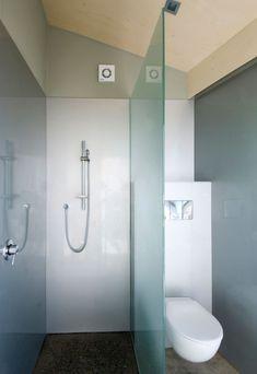 petite salle de bains sous les combles avec des parois en verre et panneaux muraux blancs