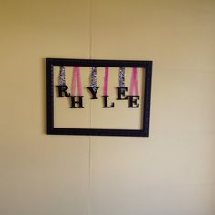 "Took an old picture apart spray painted the frame and cardboard letters and attached them with ribbon. I call this ""the name frame"" Rhys name up in her room!! thanks mamaw"