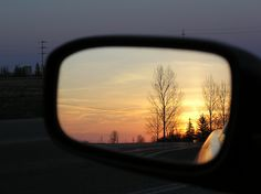 Car side mirror with a view of Sunset