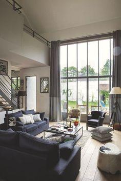 Un salon avec de larges baies vitrées