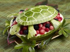 Green Turtle fruit platter ♥ cut 2/3 to 1/2 off top of watermelon; scoop out melon with melonballer or round spoon; mix with berries; with top half watermelon draw - shell, legs, head - draw shell pattern same as soccer ball, use old fashioned veggie peeler or knife/wood carving tool & carve lines. Poke holes in head for eyes, use couple of whole cloves for eyes. Ensure other half stays still by using a bowl or fabric to keep it steady; fill with fruit; place head, legs then top of shell. Voila! summer picnic, fruit bowls, fruit salads, watermelon art, summer parties, watermelon carving, 1st birthdays, fruit art, food art