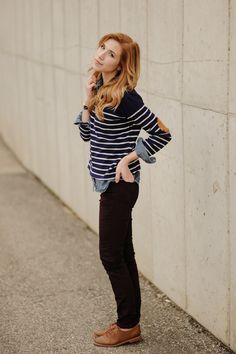 Striped sweater with elbow patches, chambray shirt, burgundy jeans, and brown oxfords.
