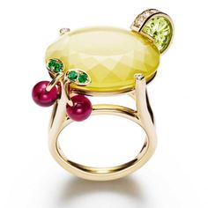 Limelight Cocktail Ring by Piaget: 18k yellow gold ring set with 13 brilliant-cut diamonds, 1 carved peridot, 1 oval yellow quartz, 4 round emeralds and 2 red rubellite beads