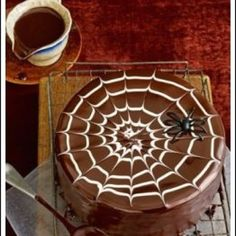 for a wickedly good spider web pour chocolate glaze over the top of a layered halloween cake none of your guests will be able to take their hands off this - Easy Halloween Cake Decorating Ideas