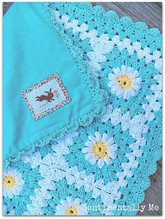 Ravelry: quiltdoggie's Baby Daisy Blanket.  I love the idea of backing it with fabric...that should help keep the afghan's shape.