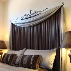 Curtain headboard! I like this! Gives the effect of a headboard and a window
