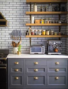 Oh my kitchen...wood open shelves with brass brackets, stunning full walls of subway tile with dark grout and lovely gray bottom cabinets with brass hardware. From new Domino Mag