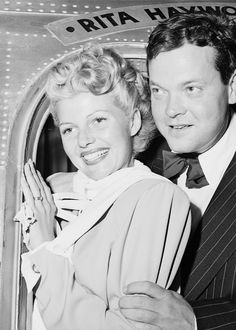 """Rita Hayworth, glamorous film star and her husband Orson Welles stand in the doorway of their plane the """"Rita Hayworth Special"""" as they left for Mexico City. They are going on location at Acapulco, Mexico for the film """"Lady From Shanghai""""."""