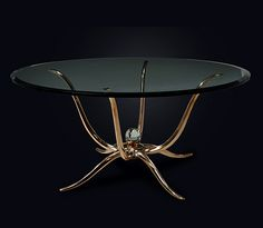 SOLID BRONZE SCULPTURAL TABLE  Art studio bronze sculptural centre table or dining table. Handmade and finished artisan solid cast bronze table with glass top. Glass top in various sizes on request. High profile couture piece. The exceptionally sculptural base emulating an octopus to include four arms terminating on stylised feet and a further four raised arms which support the table top. Predominant glass ball in the centre of the stand.