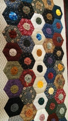 cute scrappy hexies quilted runner with yoyos added to the centers