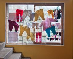 """Travel Photographer, Sivan Askayo's series """"Intimacy Under the Wires"""" photographing laundry."""