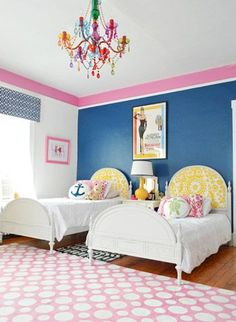 Everything from that awesome colorful chandelier (from Urban Outfitters!) to the bold blue wall with the fun pink border and some more patterned fabric cornices (plus that great geometric rug that she got on clearance from PB Teen for $150!) was completely fun and charming.