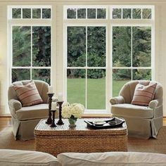 glass doors and windows looking out over a green lawn from a living room