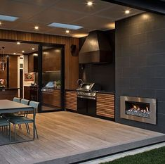 This home's kitchen flows from directly indoors to out via large glass sliding doors Stone Tile Fireplace, Outdoor Wood Fireplace, Wood Fireplace Surrounds, Fireplace Tile Surround, White Fireplace, Outdoor Fireplaces, Outdoor Seating Areas, Outdoor Living Areas, Indoor Outdoor Living