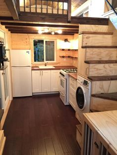 """A cozy, luxury tiny house available for sale in Bend, Oregon. The home spans 280 sq ft and features a full kitchen, living and dining room, bathroom, and two lofts with a """"dog walk""""."""