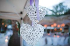 Wedding Decoration in Beach Wedding Venue, Chalkidiki, Greece. White wooden ratan hearts with lavender silk ribbons.