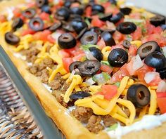 1 lb. ground beef 1 envelope taco seasoning mix 2 (8 oz.) cans Pillsbury crescent rolls 1 (16 oz.) can refried beans (I used the jalapeño kind) 2-3 cups shredded cheddar cheese or Mexican blend 1/2 cup chopped tomatoes 1/4 cup sliced black olives 4 green onions, chopped sour cream, if desired