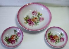 One 1920s bowl, with two matching smaller side bowls. Trimmed in a fuchsia colored Lusterware, with lovely roses in the center.