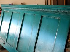 Take an old door, paint it, add crown molding of your choice - instant headboard. Love this color.