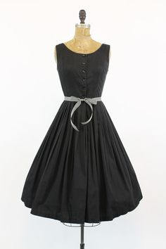 Darling 1950s shirtwaist dress! Done in a black cotton. Fitted bodice that buttons down the front. The back of bodice is made in gathered pleats.