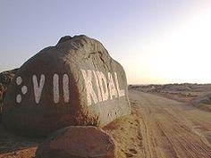 Signalisation bilingue à l'entrée de Kidal. Sur le côté gauche du rocher, Kidal est écrit en caractères tifinagh «ⴾⴸⵍ».