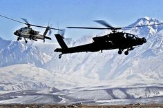 Two AH-64D Apache helicopters approach the flightline on Camp Marmal, Afghanistan, Feb. 7, 2012, as snowcapped mountains provide a backdrop.