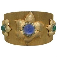 Rare Buccellati 14k yellow gold wide cuff bracelet with three flower designs,decorated with 14.15ct sapphire cabochon and two emerald cabochons 3.34ctw. Comes with Replacement value certificate from B
