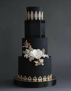 black tiered cake with white and gold flowers and medallions
