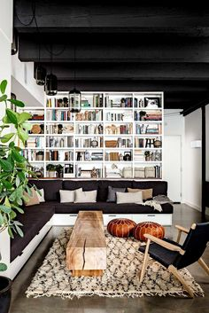 Living room: built-in white bookshelves above built-in black and white sofa; black ceiling with exposed beams, polished concrete floor, wooden bench as coffee table, black glass pendant lights