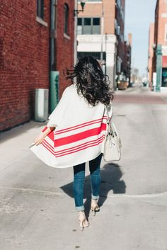 Striped Poncho Cardigan hybrid by Cupcakes and Cashmere. Can be styled with jeans and heeled sandals for a casual chic look, or with a dress in a contrasting color. A versatile piece great for spring, summer and fall. Having movement in the cardigan adds depth to a look.