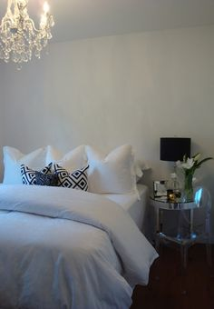 Gorgeous bedroom with crystal chandelier, crisp white bedding with David Hicks La Florentina pillows, Kartell Ghost Chair, mirrored tiles round table nightstand and tulips.