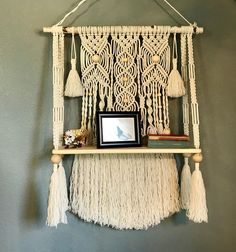 """This is a macrame wall hanging with a natural wood shelf attached. The shelf measures 27""""w x 7.5d x 1""""thick. The macrame is attached to a birch branch measuring 31"""" wide. The macrame design measures 40""""long x 27""""wide and is made with 100% cotton rope in a lamb's wool color. The"""