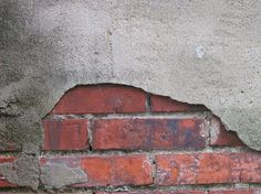 Red brick under crumbling stucco.