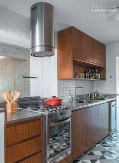 Apartamento de 88 m²: menos paredes, sob medida para uma jovem - Na cozinha, piso de ladrilho hidráulico (Casa Franceza) e marcenaria de cumaru (Marvelar). O fogão dá para a bancada, permitindo a interação entre quem cozinha e quem está na sala.