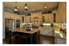 Dark cabinets in the island contrast with white main cabinetry. The Hartford II plan by Drees Custom Homes. The Crystal Falls Grand Mesa community. Leander, TX.
