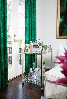 A vintage inspired bar cart + emerald green drapes.