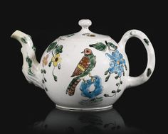 A STAFFORDSHIRE SALT-GLAZED STONEWARE TEAPOT AND COVER, CIRCA 1750 of small size, with a crabstock handle and spout, brightly enamelled with a bird perched on a pierced rock surrounded by flowers, minor restoration and chips.